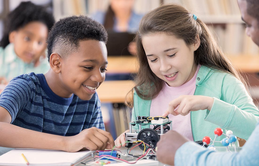 Two kids learning about a robotics project from a teacher