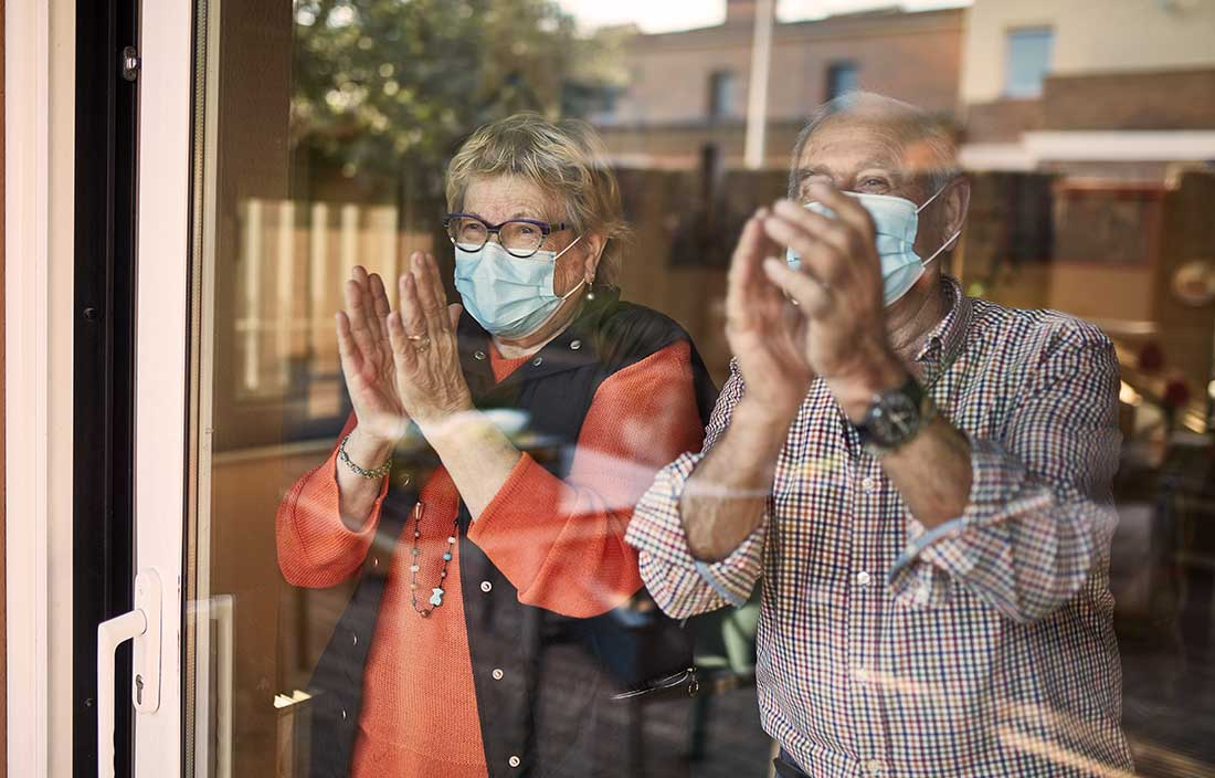 Two seniors with COVID medical masks looking out their senior living home window and clapping