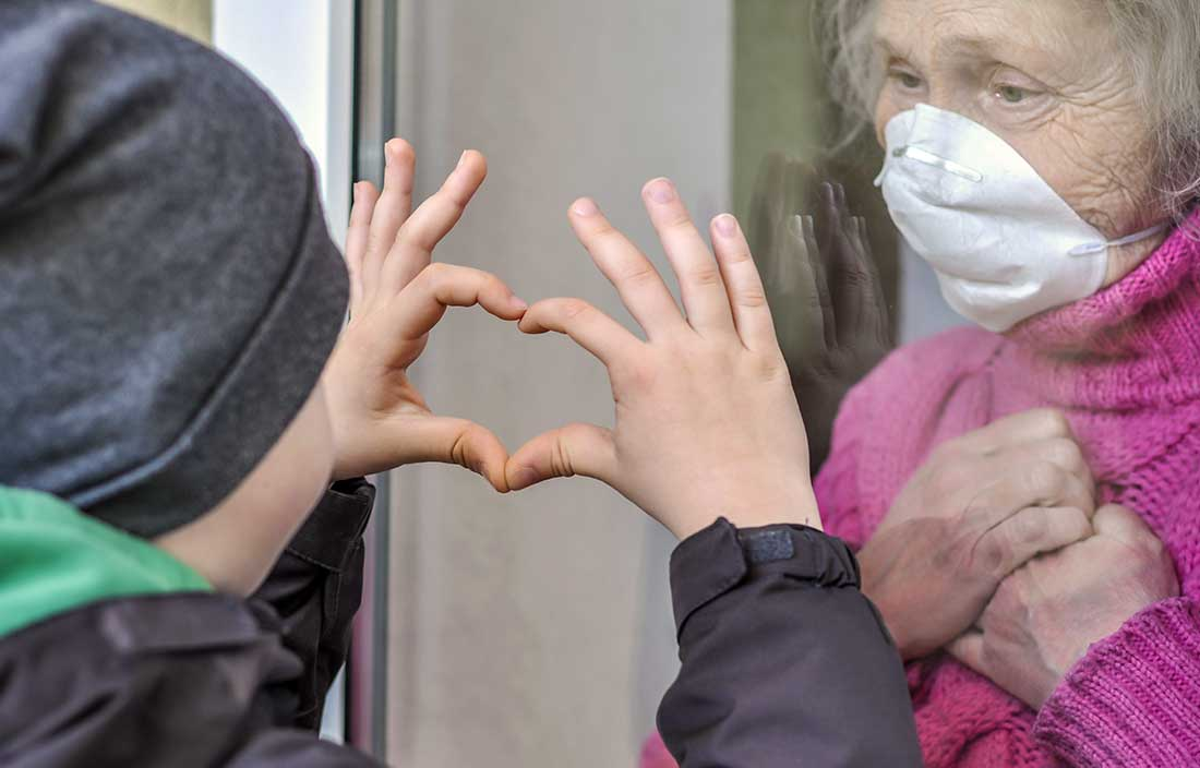 Senior living resident visits with her grandson through a window as he hold up his hands in a heart