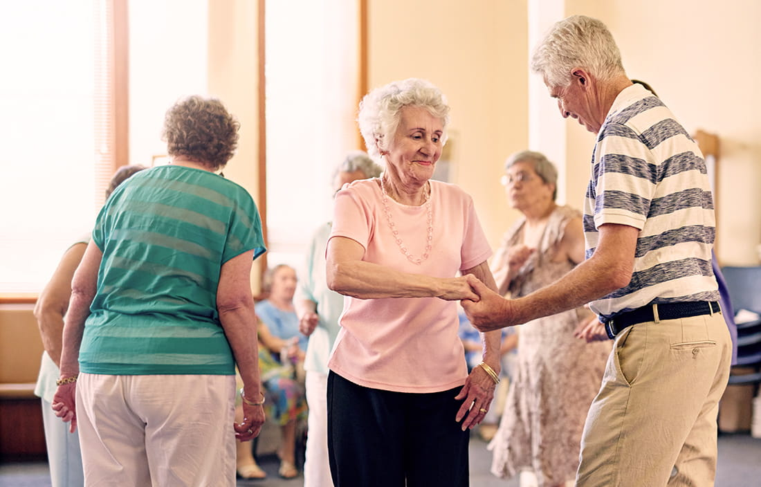 Seniors at an adult day care center dancing in a large, well-lit room