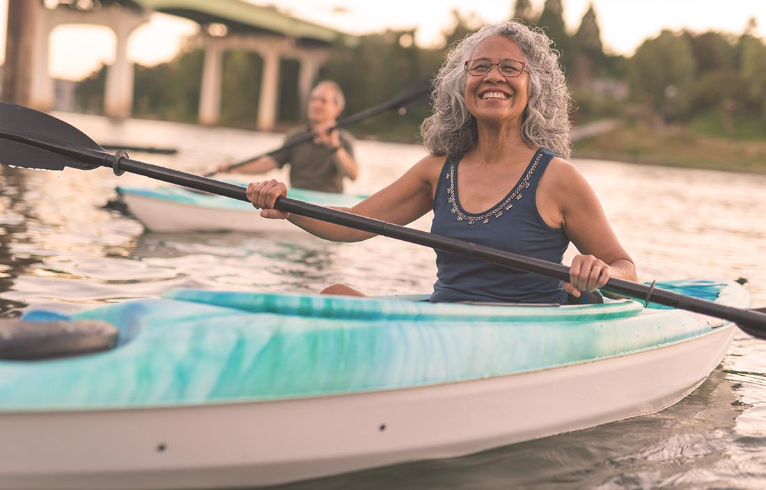 Younger older adult seniors kayaking in a river living an active adult lifestyle