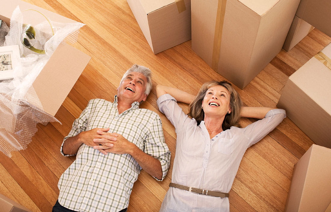 Happy baby boomer couple lying on the floor of their new home in an active adult community