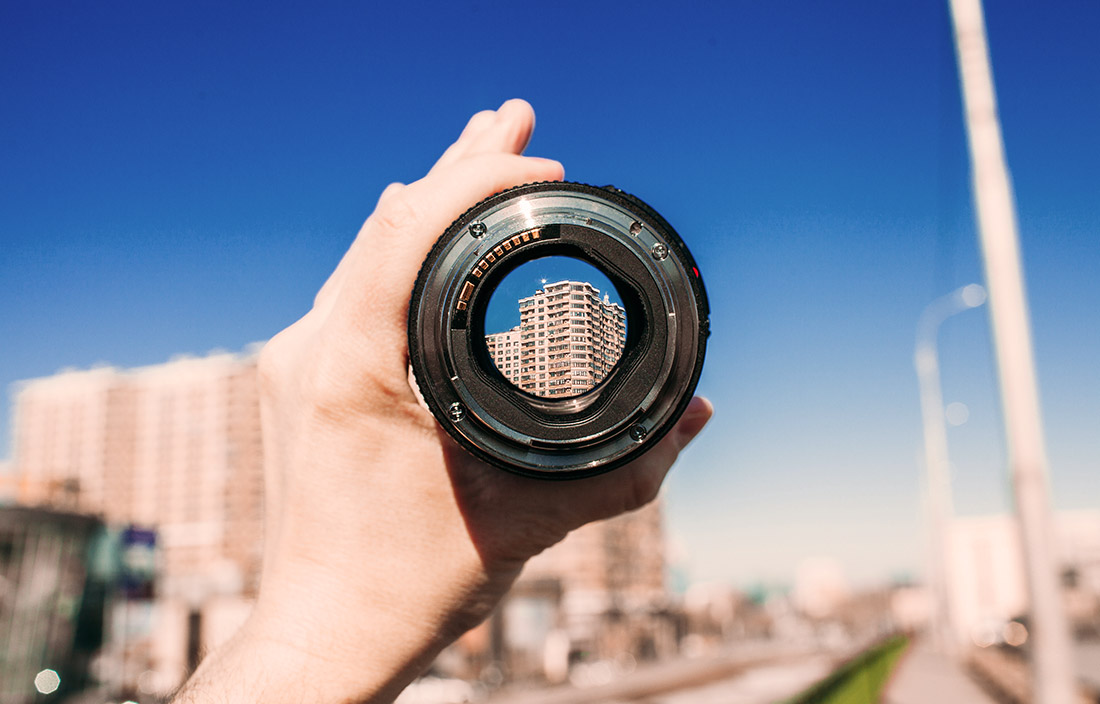 hand holding a lens in front of a blurry city building and road where through the lens a building can be seen clearly