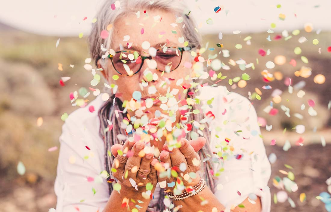 Senior woman blowing confetti to show excitement for new construction on senior living campus