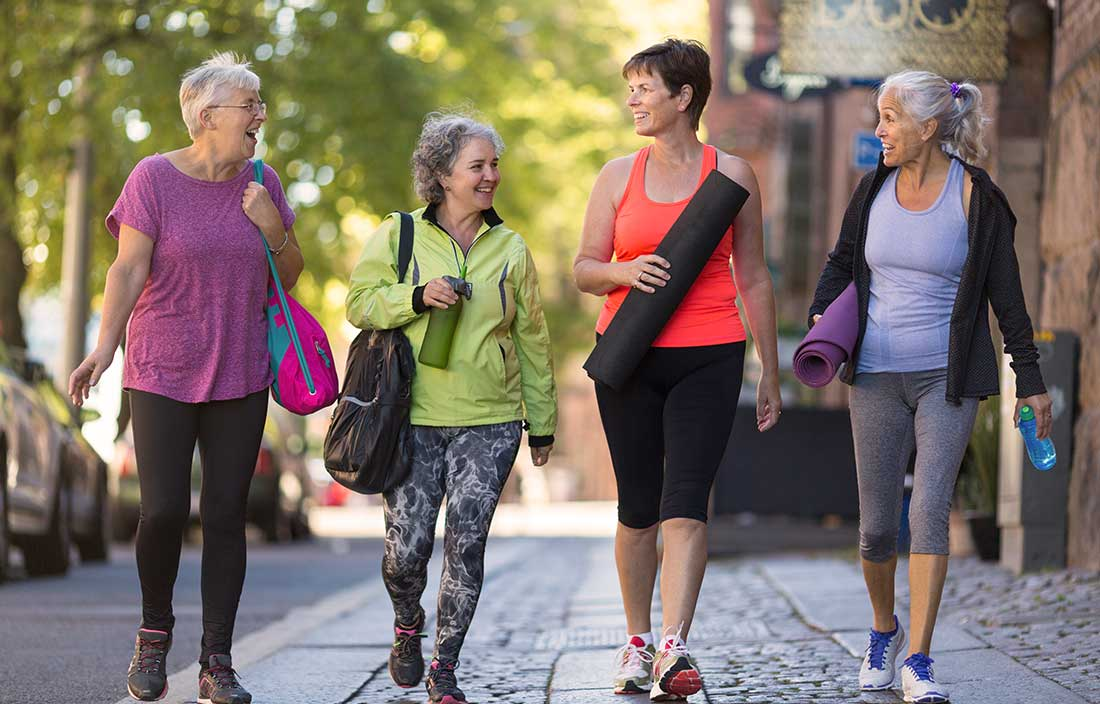 Older adults talking and walking down a street in fitness clothes to their active adult home