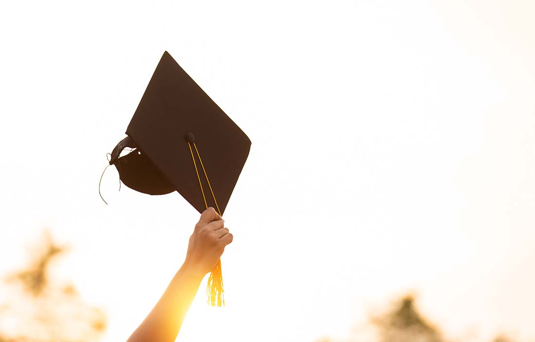 Hand holding up a graduation cap into the air with an abstract, brightly lit background