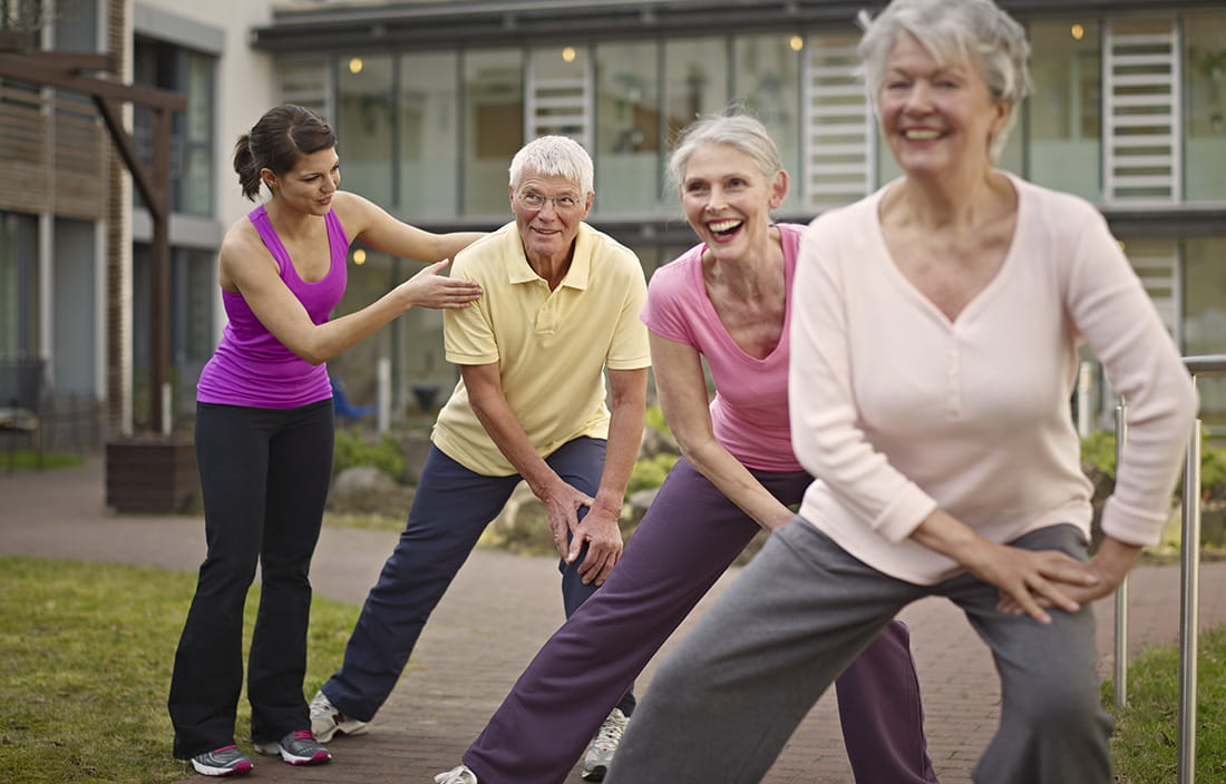 Senior living community staff engaged in a meaningful wellness and fitness activity with a group of seniors