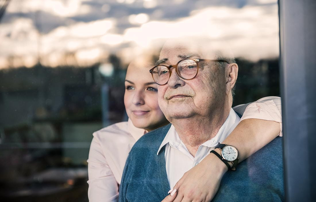 Senior and adult daughter worrying about affording senior living while looking out a window together