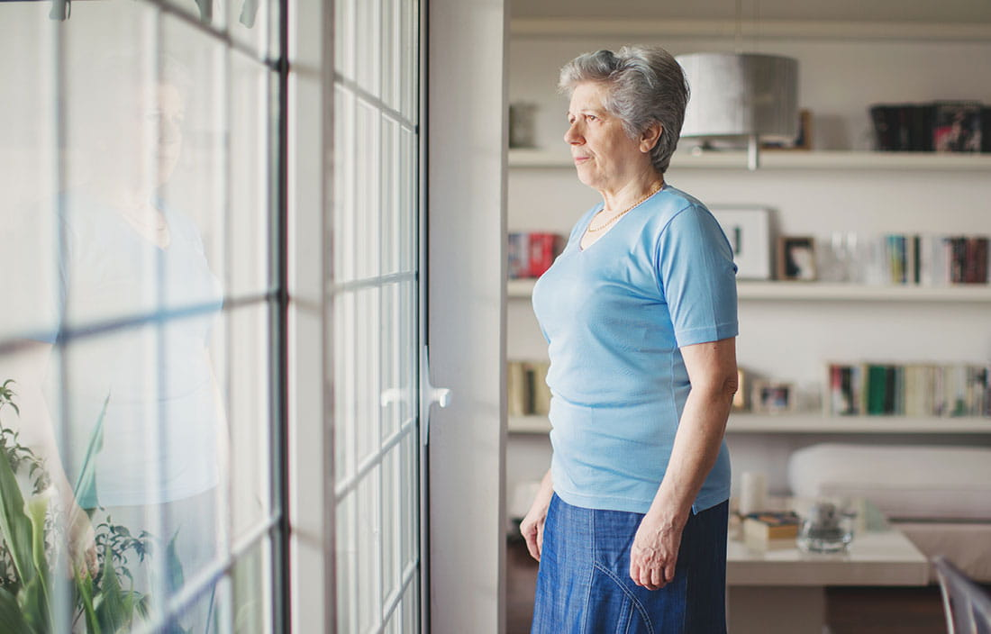 Senior woman looking out the window of her home, concerned