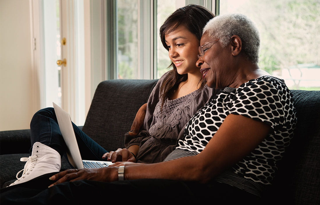 Senior woman and young girl looking at a computer while sitting on a couch