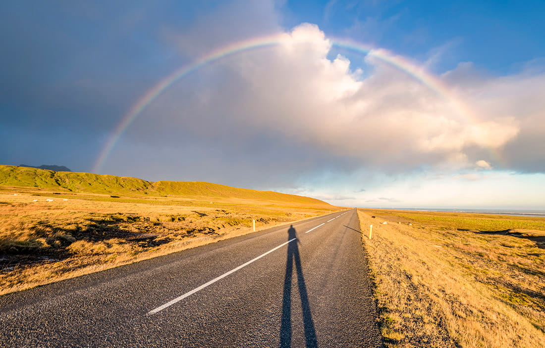 Shadow stretched out on a desert road leading to the horizon under a rainbow