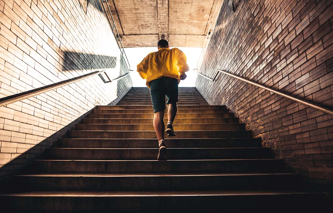 Senior man in a yellow jacket running up enclosed stairs toward a bright light