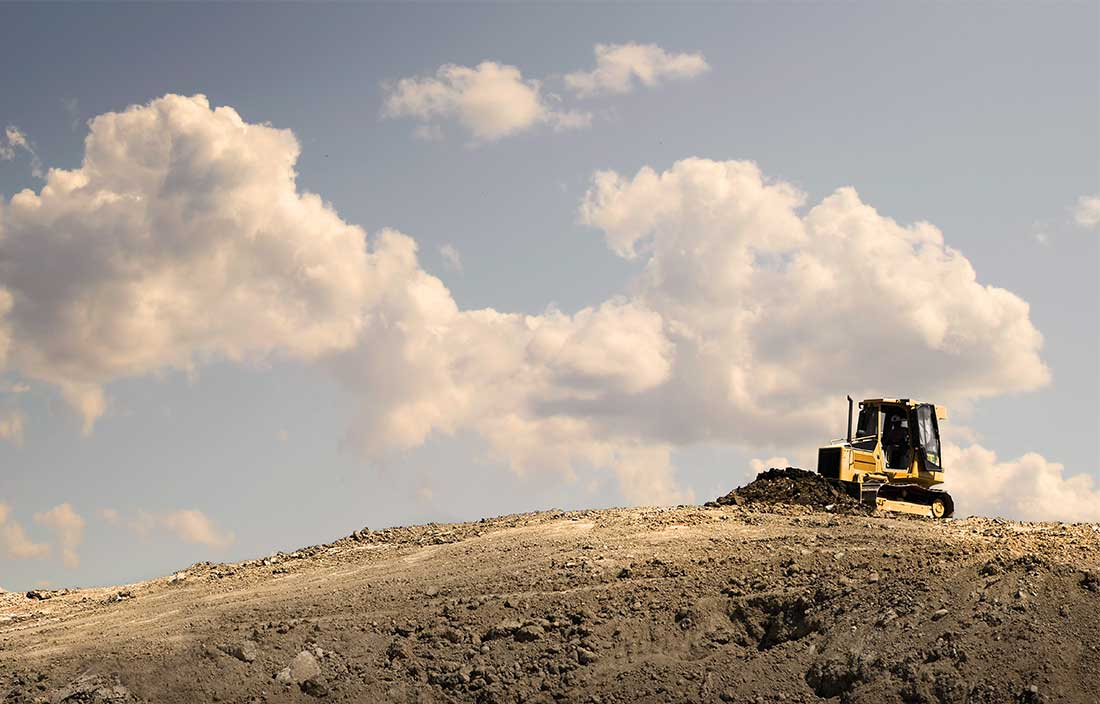 Bulldozer working on a hill of dirt for a new development