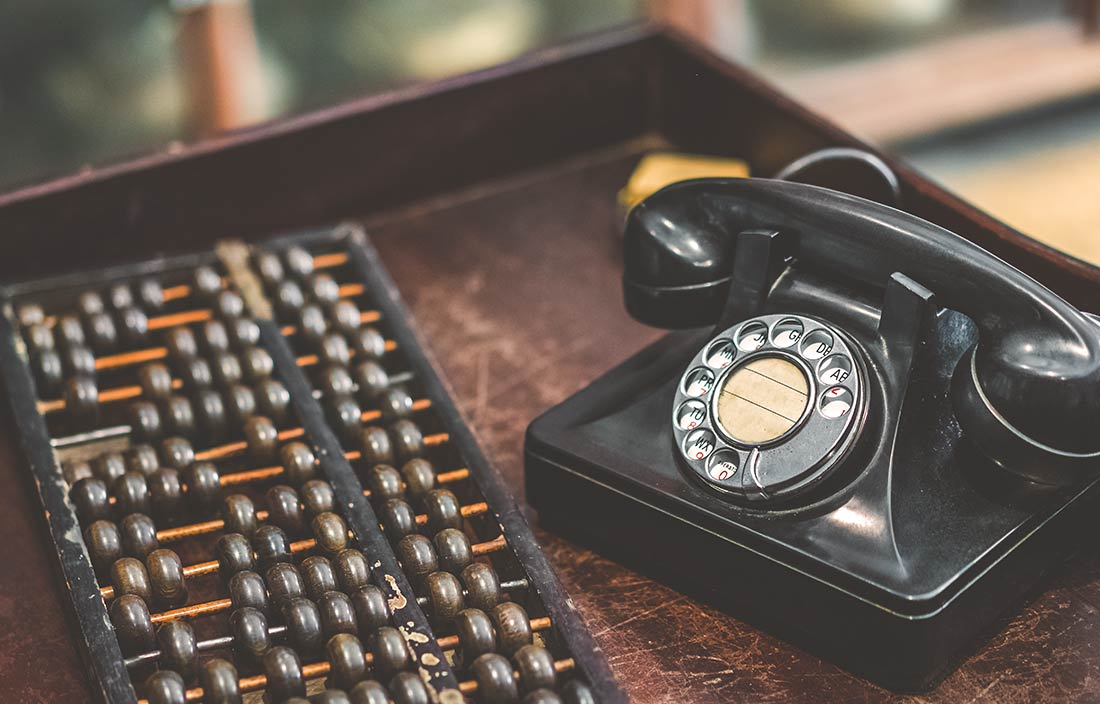Abacus and old-style telephone represent a change in how people do things over time