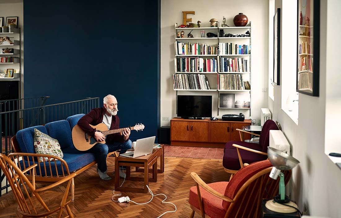 Older adult senior playing guitar while look at a laptop in a modern independent living senior living apartment