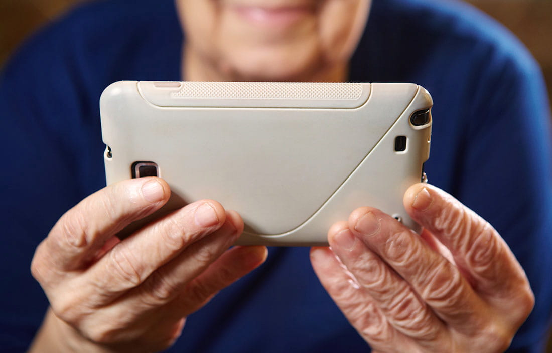Image of older lady holding a smart phone to show how technology is changing senior living