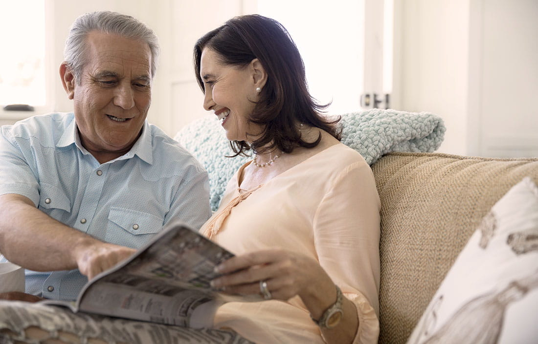 Senior couple sitting on a couch reading a senior housing brochure