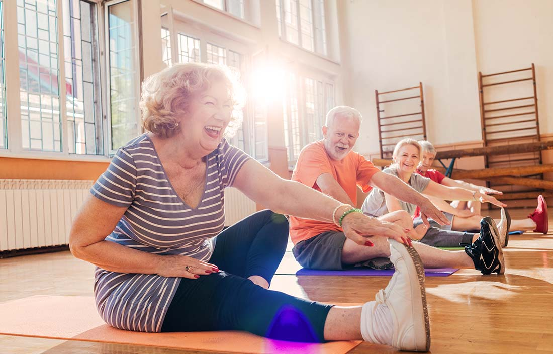 Seniors stretching in a gym during a wellness class at a senior living community