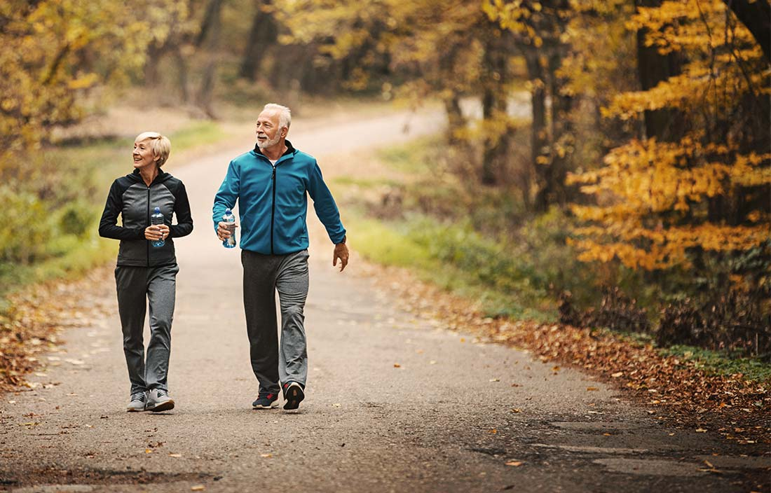 Two active senior adults walking next to a forest in fall