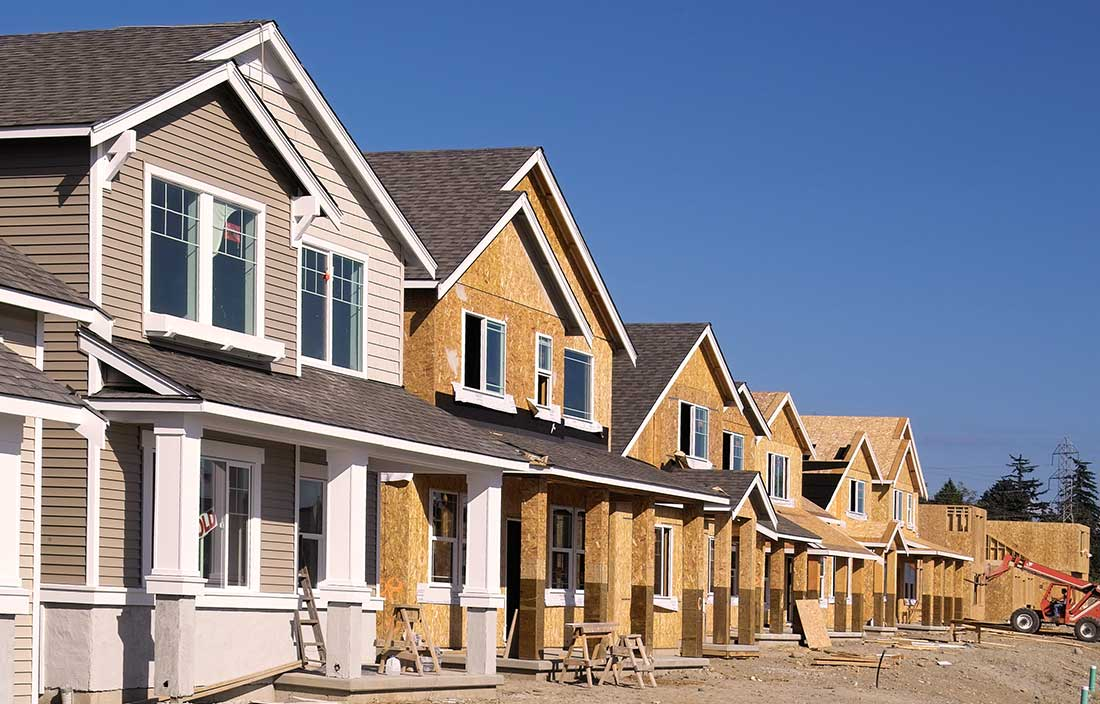 Senior living development of repositioned homes, with one home complete and sold and the others along the street under construction
