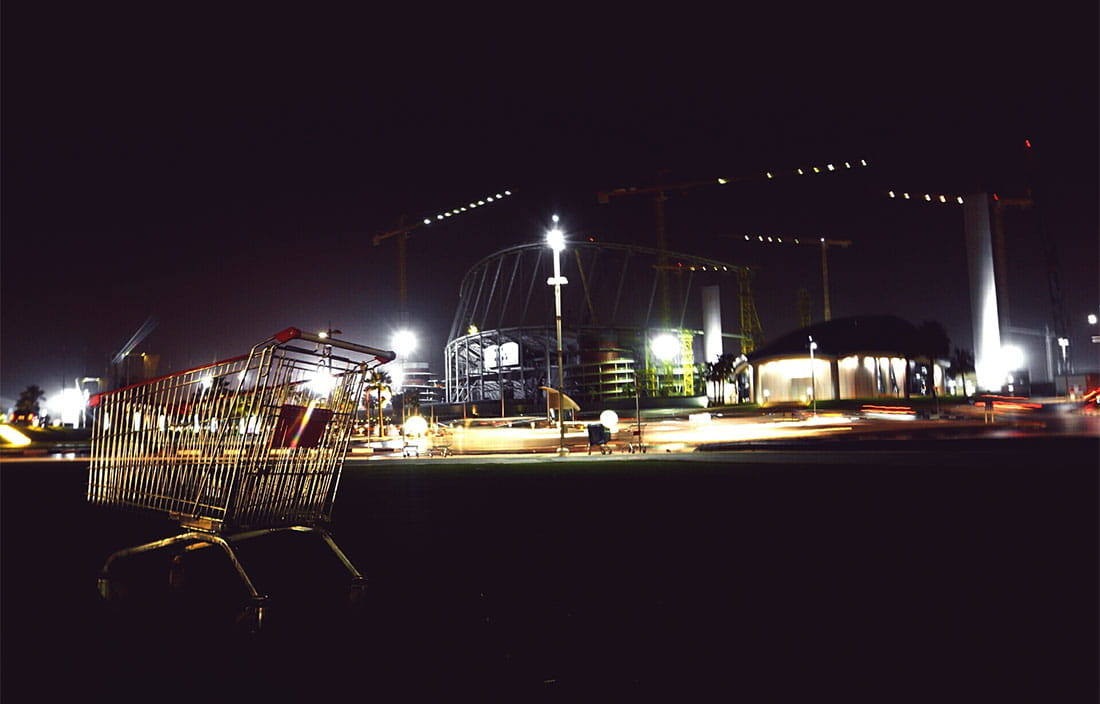 exterior of shopping center at night with cart in the foreground