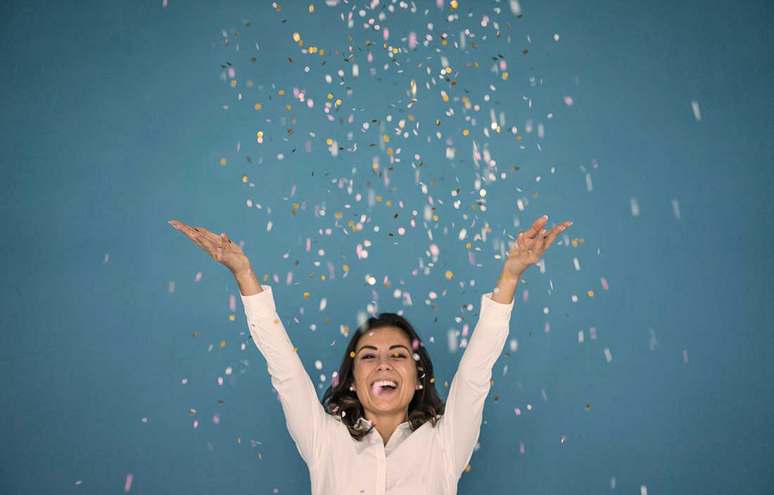 Office woman throwing confetti in the air on a blue background to celebrate award