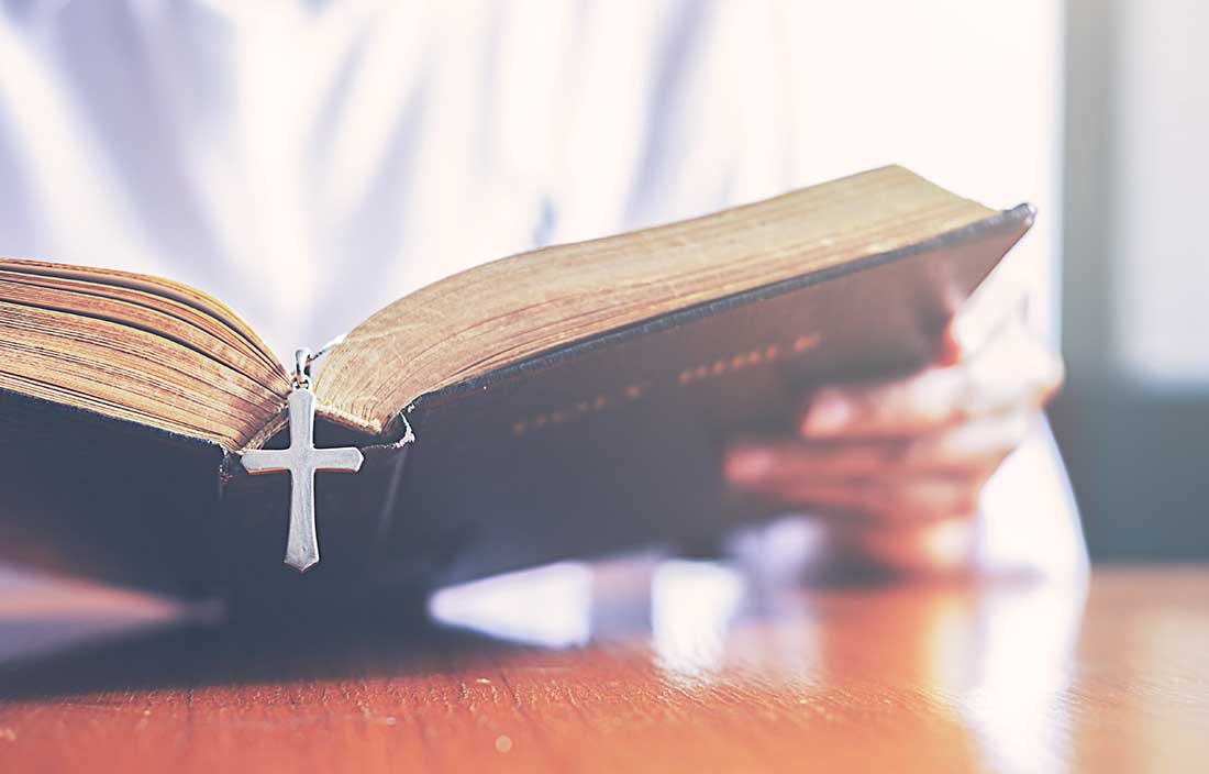 Close up of a person reading a bible at a table