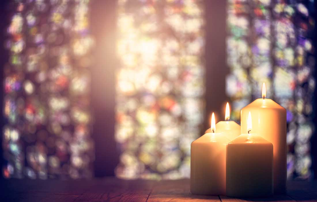 Three candles in a church with stained glass in the background