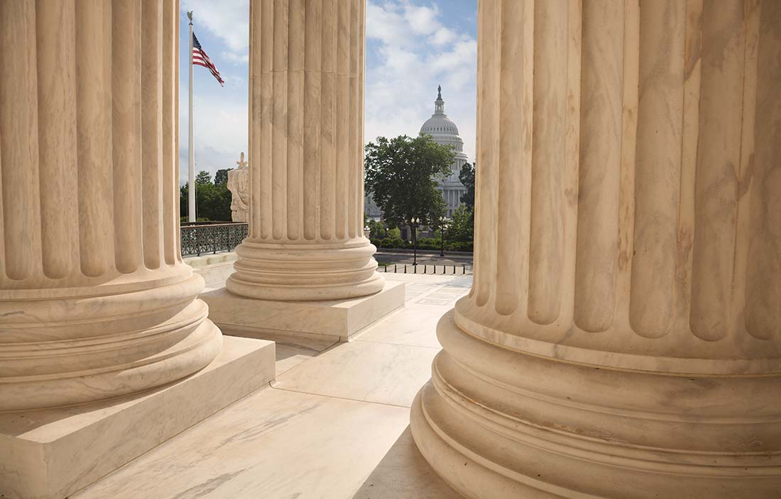 Capitol Building Seen Through Columns of the Unites States Supreme Court Building