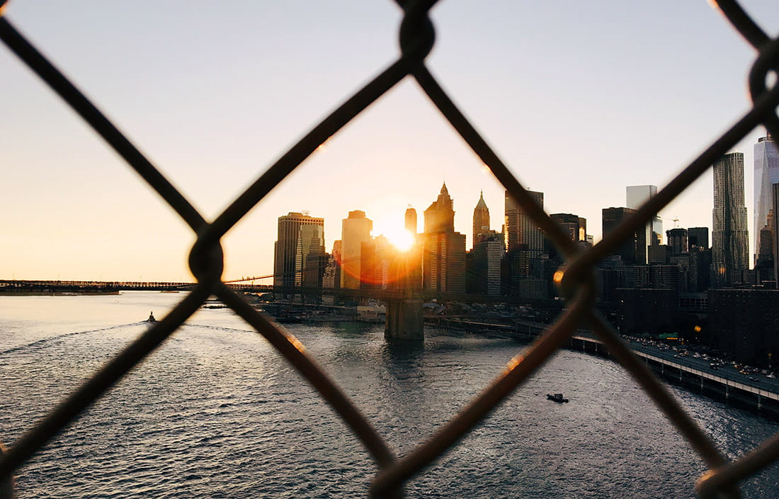 Image of the New York harbor at sunset through a chain link fence