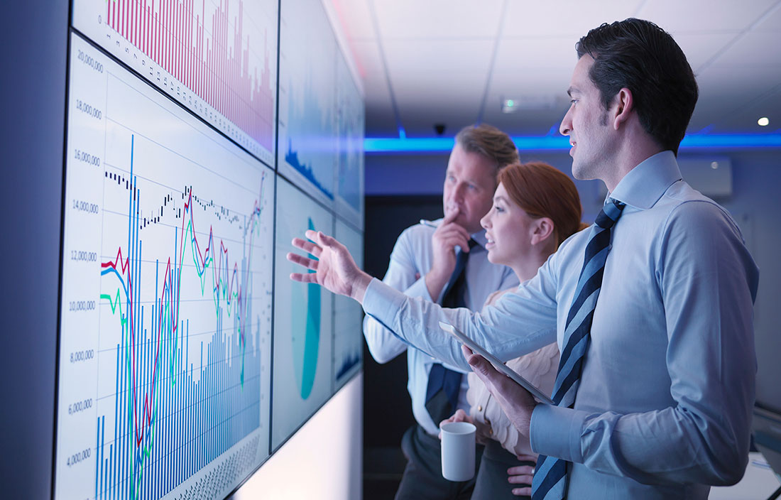 Plante Moran Market Perspectives - Three business people discuss graphs on screen in meeting room