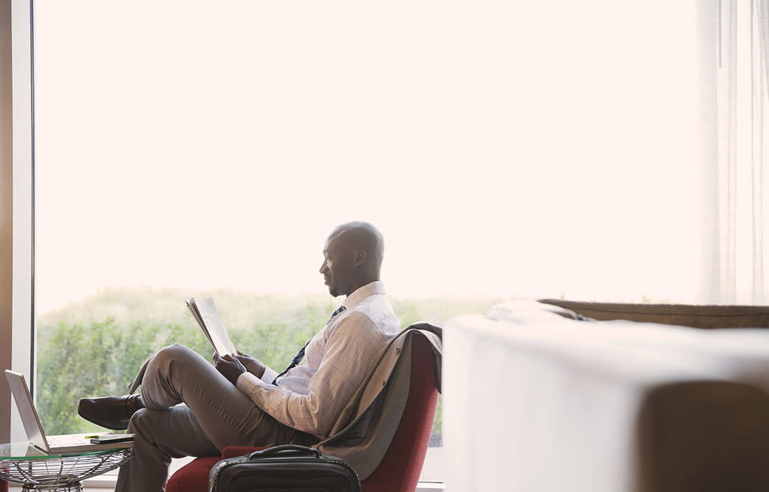 Image of a man sitting on a chair and reading a newspaper, with a window in the background.