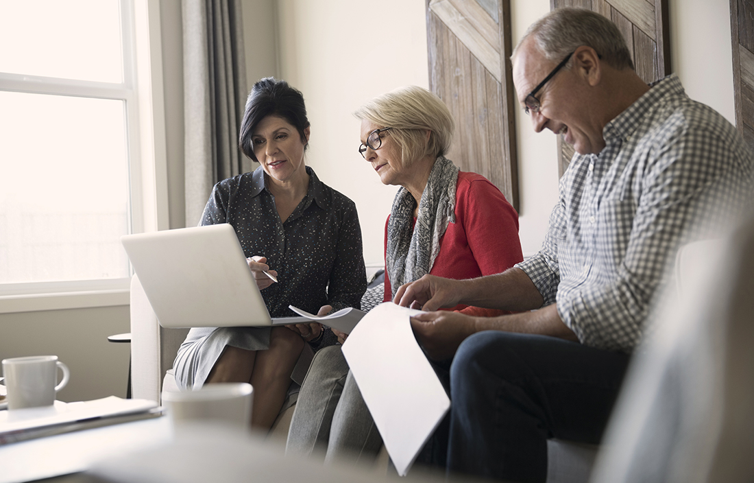 A woman is sitting with an elderly couple as they review her laptop and paperwork in their hands.