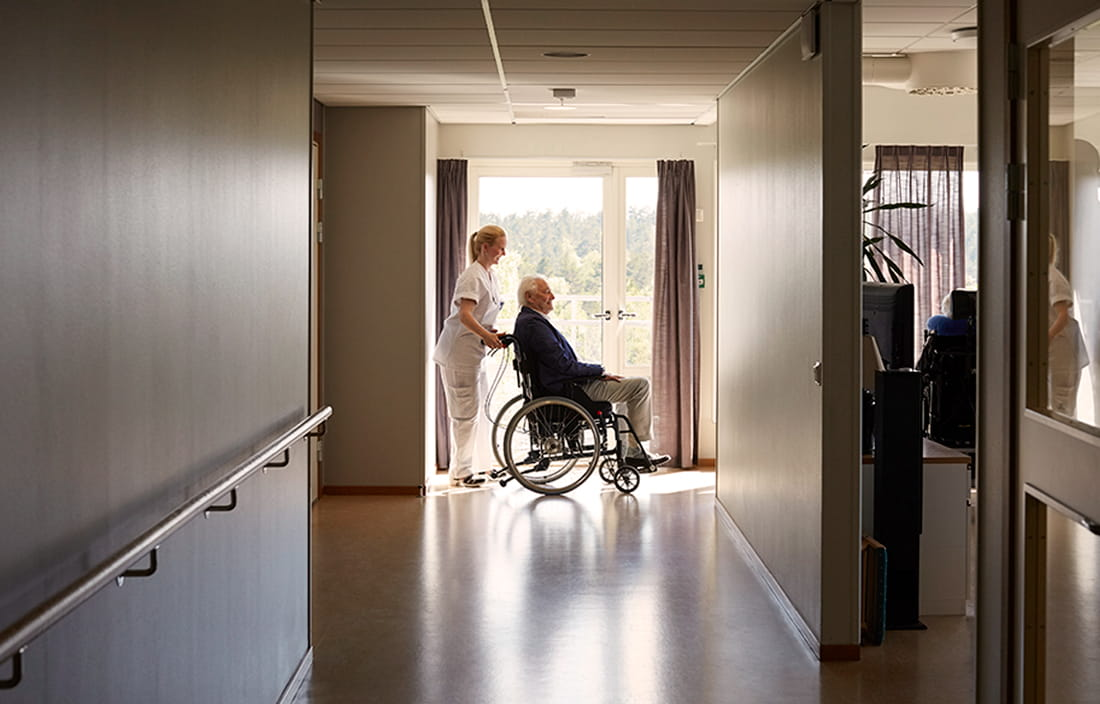 Nursing assistant pushing an elderly senior citizen in a wheelchair through a hospital hallway.