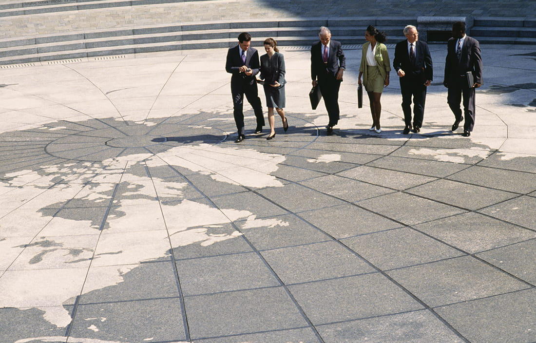 Group of business colleagues walking on a globe designed pavement.