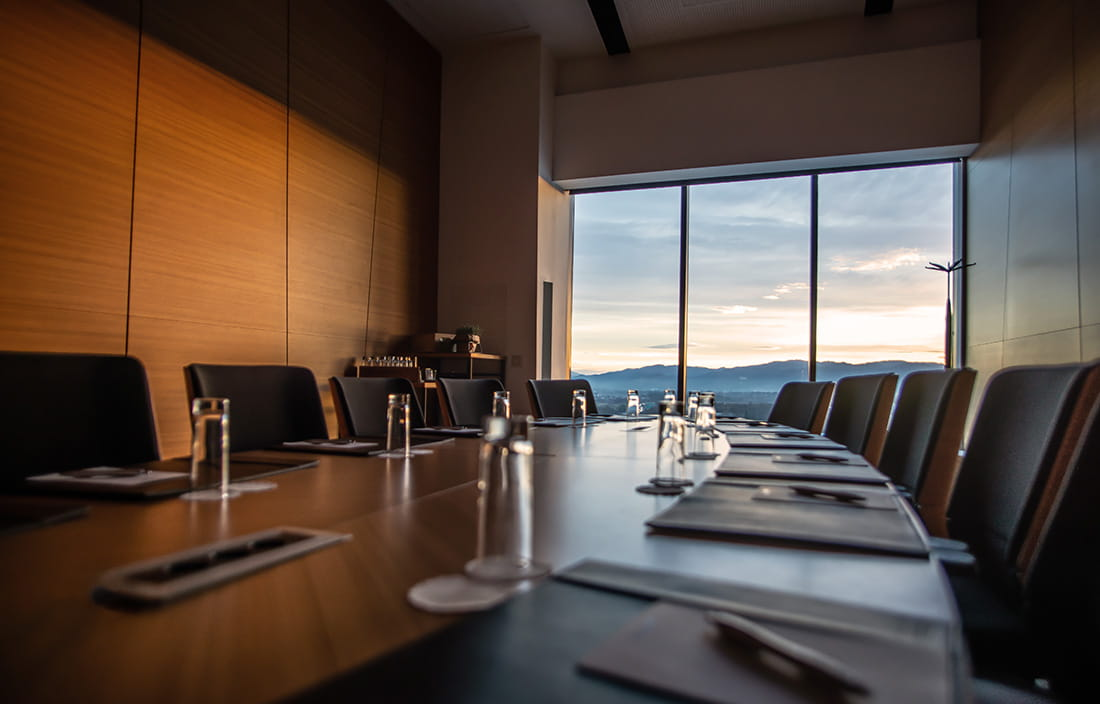 Close-up photo of a conference room desk with a view of a sunrise outside the window in the background.