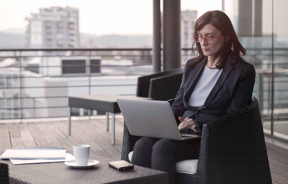 Middle-aged businesswoman using her laptop computer in an outdoor area.