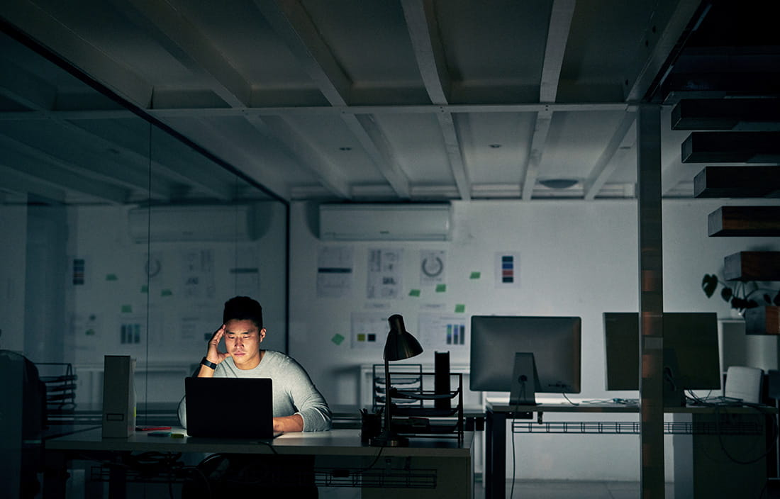 Younger male worker sitting in a dark office working on his laptop computer.