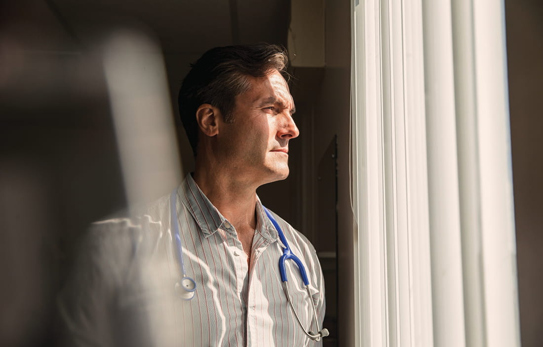 Man wearing a stethoscope while looking out a window.