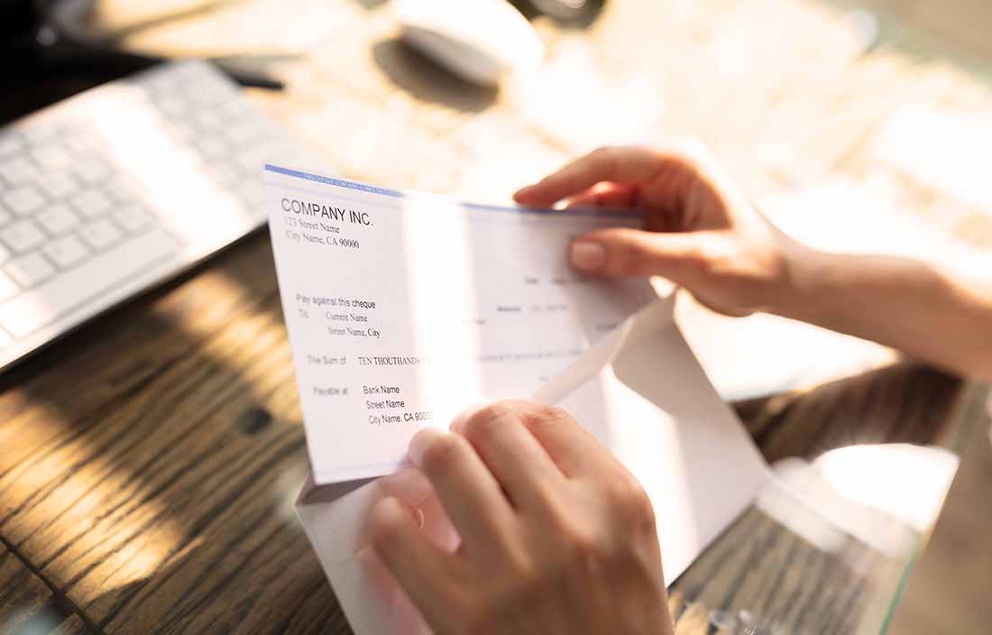 Close-up photo of hands opening a letter and holding a check.