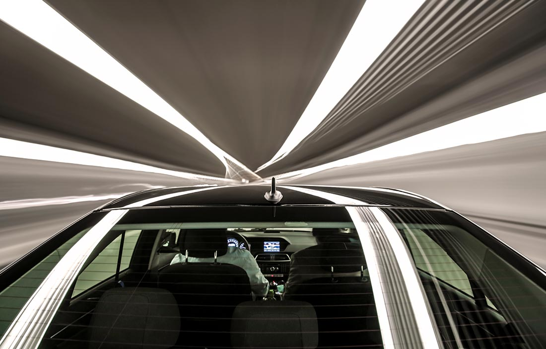 Top view of a futuristic high-end car traveling through a tunnel.