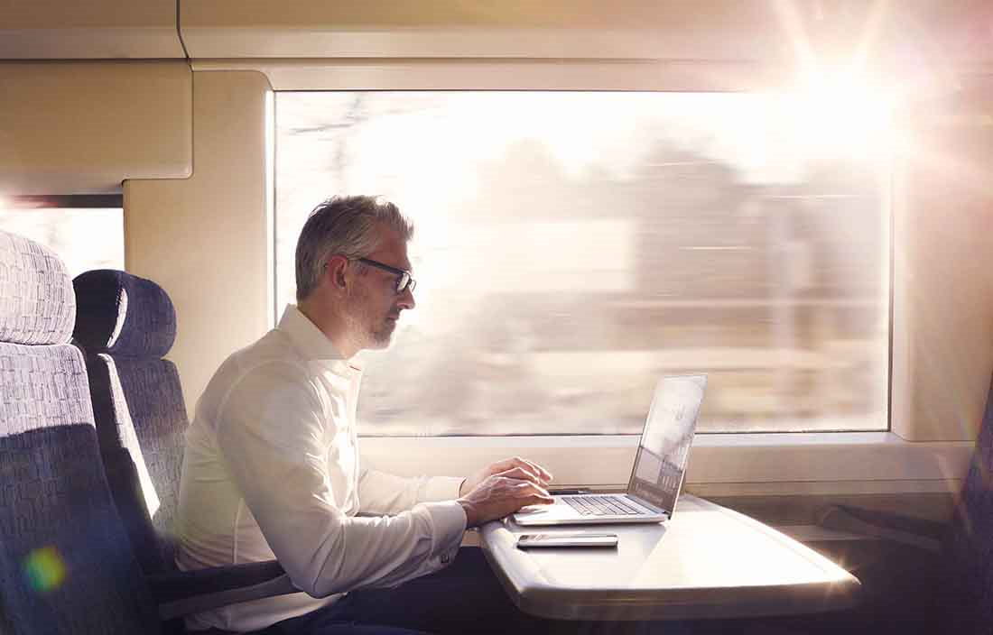 Businessman working on his laptop computer while on a train.