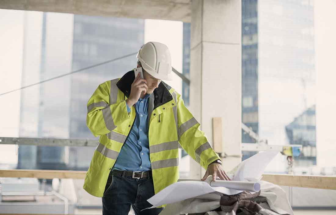Construction worker in a hard hat viewing blueprints and planning documents.
