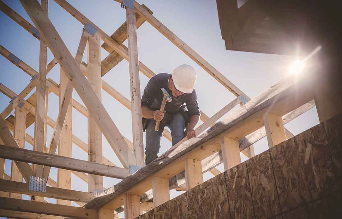 Construction worker working on a roofing segment of a house.