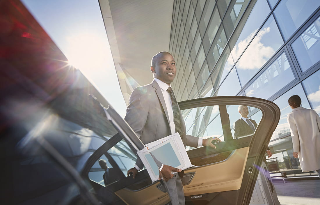 Man in business suit exiting a futuristic car.