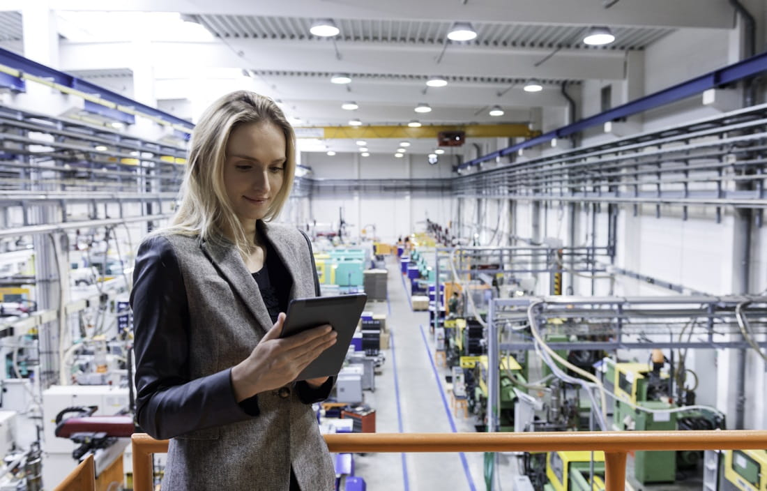 Image of a woman holding a tablet computer with a manufacturing plant behind her.